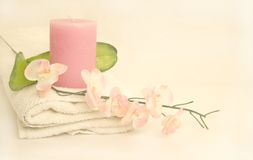 Oriental Blossom Spa. Oriental Orchid blossom on white spa towel and scented pink candle in high key cleansing concept Stock Image