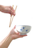 Oriental bowl and chopstick. Hand with wooden chopsticks food bowl traditional cultural china oriental ricebowl isolated white background Royalty Free Stock Images