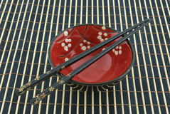 Oriental bowl and chopsticks Stock Image