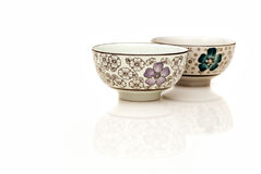 Oriental bowl with reflection. Two hand painted oriental soup bowl on white background with reflection. A bowl is a round, open-top container used in many Royalty Free Stock Images