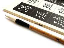 Oriental calligraphy brush. An image of a chinese calligraphic brush beside a book for learning about calligraphy.  Open page of book shows standard way of how Royalty Free Stock Photography