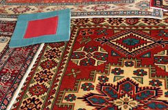 Oriental carpets. Heaps of valuable oriental carpets and a carpet with a red square Stock Photos
