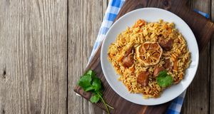 Oriental cuisine. Uzbek pilaf or plov from rice and meat. Wooden rustic background. Top view vith copy space royalty free stock photography