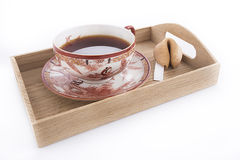 Oriental cup of tea with fortune cookie. Isolated oriental cup of tea with fortune cookie on wooden tray Stock Photography