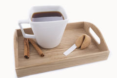 Oriental cup of tea with fortune cookie. Isolated oriental cup of tea with fortune cookie on wooden tray Royalty Free Stock Image