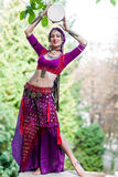 Oriental Dancer. With tambourine in the park Royalty Free Stock Photo
