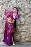 Oriental Dancer. A woman performer of oriental dances in the backdrop of a stone wall Stock Image