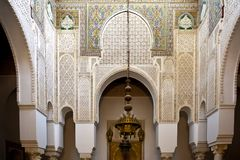 Oriental decor in Tarfaya Mosque in Meknes, Morocco, craftsmanship oriental scarved marble. Oriental mosaic tiles and scarved marble wall decoration in Tarfaya Royalty Free Stock Photography