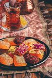 Oriental delight rahat lokum with tea in armudu. Over tablecloth with ornament stock photos