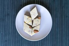 Oriental dessert halva with pistachio, almond, cashew nuts, peanut, walnut  on a  plate. Image. Healthy food. closeup of sweets. From Iran popular in many other royalty free stock image