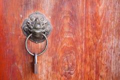 Oriental door knocker. Antique oriental door knocker on wood door Royalty Free Stock Image