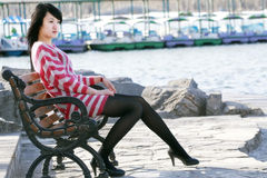 An Oriental girl. A Chinese girl sits on the chair appreciating the beautiful scenery silently Royalty Free Stock Photos