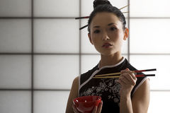 Oriental girl with chopstick. Nice back light shot of a beautiful asian girl in japanes dress eating and using chopstick stock photography