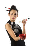 Oriental girl with chopstick. Beautiful asian girl in japanes dress and chopstick showing a red cup royalty free stock image