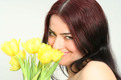 Oriental girl with flowers. Oriental pretty girl dancing with yellow tulips Stock Images