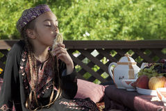 Oriental girl has breakfast with flat cake Stock Photography