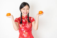 Oriental girl in red qipao holding mandarin orange Royalty Free Stock Image