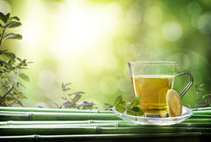 Oriental green tea with mint and lemon on bamboo front Royalty Free Stock Photography