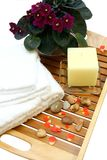 Oriental health and bodycare. A spa or health/bodycare setting consisting of a candle and white towels with scattered pebbles and rose petals Royalty Free Stock Photo