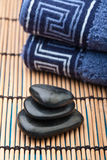 Oriental hotstone treatment. Pile of hotstones with blue towel on bamboo mat Royalty Free Stock Photos