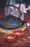 Oriental tea. Oriental inspired elements, like a typical iron teapot, tea cups, bamboo sheet, sakura or cherry blossom and a paper umbrella, combining elements Stock Image
