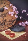 Oriental tea. Oriental inspired elements, like a typical iron teapot, tea cups, bamboo sheet, sakura or cherry blossom and a paper umbrella, combining elements Stock Photos