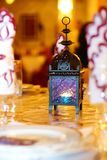 Oriental lamp on a table. At wedding, with out of focus napkins Stock Image