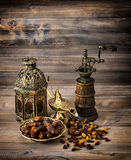 Oriental lantern and mill. Raisins and dates on wooden background Royalty Free Stock Images