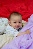 Oriental lovely baby. Crawling Clever Oriental baby on the bed and Cheerful  expression on his face Royalty Free Stock Photos