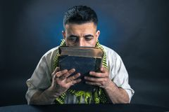 Oriental man in traditional national Arab dress kisses an old big book.  royalty free stock photos