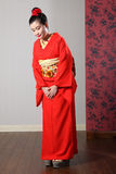 Oriental model in red Japanese kimono bowing Royalty Free Stock Photography