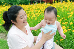 Oriental mother and her Child playing in garden Royalty Free Stock Photography