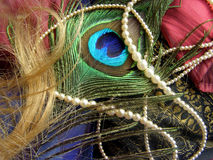 Oriental motive. Necklace from ocean pearls, various kinds of textiles, blond hair, quill, peacock butterfly Royalty Free Stock Image