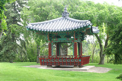 Oriental pagoda in park. Exterior of oriental pagoda structure in park with trees in background royalty free stock images
