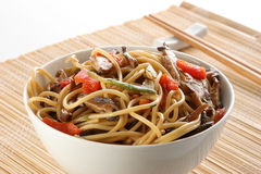 Oriental pasta. Recipient with oriental pasta recipe, with shiitake mushrooms, vegetables and chopsticks, in a isolated background Royalty Free Stock Images