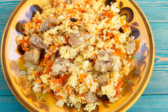 Oriental pilaf, rice with meat and carrot on yellow plate. On blue wooden table Royalty Free Stock Image