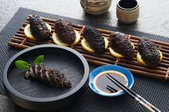 Oriental seafood. On a bamboo mat with a bowl of sauce and chopsticks Stock Photos