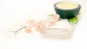 Oriental Spa Simplicity. Oriental orchid blossom, relaxing spa candle and white bath towel Royalty Free Stock Photography