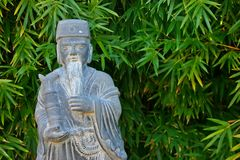 Oriental statue. Of bearded man in traditional clothing with green bamboo plants in background Stock Photos