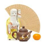Oriental still life.focus on teapot. Teapot,mandarine,porcelain shtof and fan back Royalty Free Stock Photos