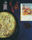 Oriental still life with homemade pie, spices and page of vintage book from Asia. Royalty Free Stock Photography