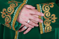 Oriental style. Hands of man in green oriental clothes embroidered with gold Royalty Free Stock Image