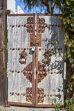 Oriental style double gate to home`s courtyard. Vintage craftsmanship displayed on sun bleached wood doors stock image