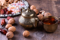 Oriental sweet on silver plate. Turkish delight, halva, dates and others. Traditional arabic tea set, walnut and dried dates. Oriental sweet on silver plate Stock Photography