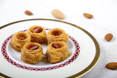 Oriental Sweets Background. Oriental Sweets - kunafa in a plate on white wood background Stock Photography