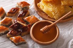 Oriental sweets: baklava with poppy and nuts and a honeycomb. Royalty Free Stock Photos