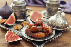 Oriental sweets with coffee. Cup of coffee with dry dates on metal oriental tray Stock Photos