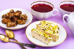 Oriental sweets-halva and dates on bright pink background. Studio Photo royalty free stock images