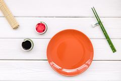 Oriental table set up with plate and bamboo sticks for sushi and maki on white background top view space for text. Asian food cooking concept. Oriental table set royalty free stock photos