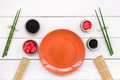 Oriental table set up with plate and bamboo sticks for sushi and maki on white background top view space for text. Asian food cooking concept. Oriental table set royalty free stock images